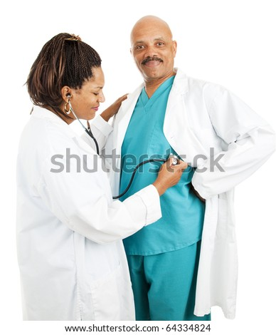 Cute african-american doctors.  She's pretending to give him a checkup.  Isolated on white.