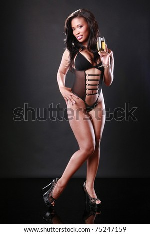 Cute African-American in black swimsuit holds a sparkling flute - stock photo