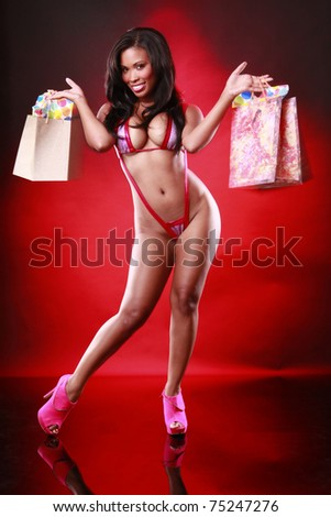 Cute African-American in red swimsuit swings her shopping bags - stock photo