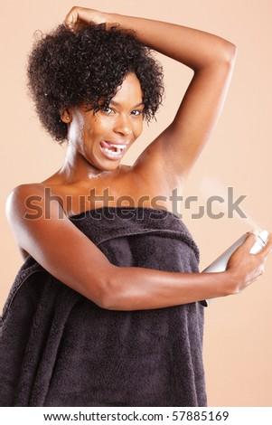 Cute African American using aerosol deodorant - stock photo
