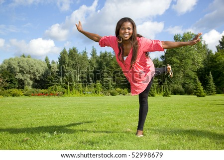Cute African American woman having fun on grass - stock photo