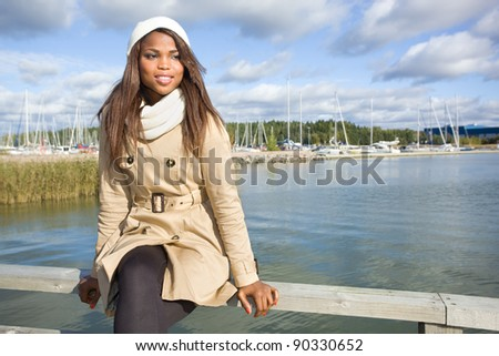 Cute african american woman sitting on a pier