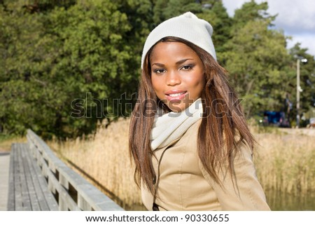 Cute african american woman sitting on a pier - stock photo