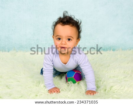 Cute African baby boy crawling in his little jeans - stock photo