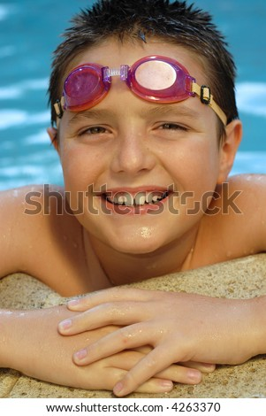 Cute All-American boy in the pool in swimming goggles - stock photo