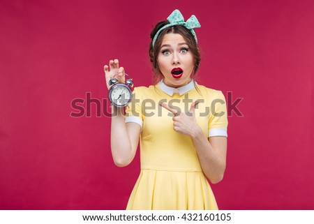 Cute amazed pinup girl pointing on alarm clock over pink background - stock photo