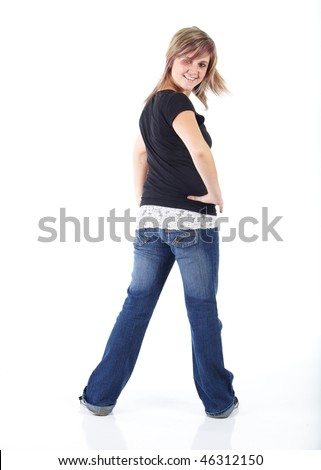 Cute and active young adult caucasian woman wearing a black top and blue jeans and with short brunette hair on a white background. Not Isolated - stock photo