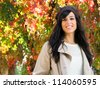 Cute and beautiful young brunette woman enjoys autumn on colorful leaves background - stock photo