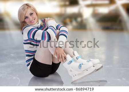 cute and blond girl with shorts and a nice sweater sitting with ice skates on