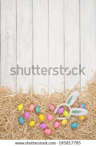 Cute and Colorful Easter Egg on Hay on Rustic White or Gray Board Background with room or space for copy, text.   Vertical - stock photo
