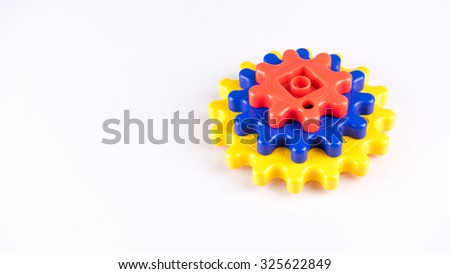 Cute and colourful plastic gears or cogwheel on white background. Concept of process and rotating mechanism. Slightly de-focused and close-up shot. Copy space. - stock photo