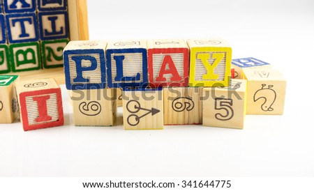 Cute and colourful wooden block forming word PLAY. Concept of fun education. Isolated on white background. Slightly de-focused and close-up shot. Copy space.