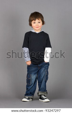 Cute and hip little preschooler boy with big brown eyes smiling with hands in his jeans pockets over grey background. - stock photo