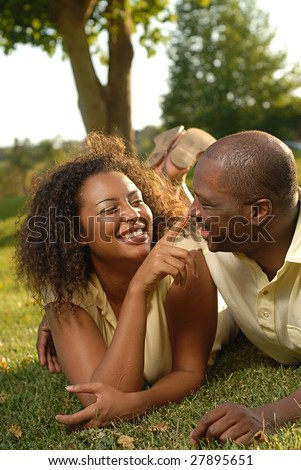 Cute and loving couple playing around on the lawn - stock photo