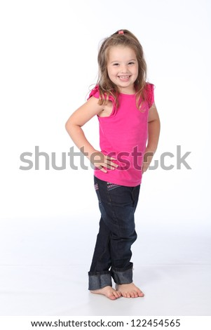 Cute and pretty little girl having a photo shoot wearing jeans and pink t-shirts on a white seamless high key background - stock photo