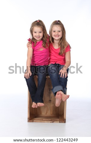 Cute and pretty twins and sisters having a photo shoot wearing jeans and pink t-shirts on a white seamless high key background, sitting on a wooden crate - stock photo