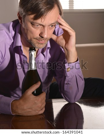 Cute and sad young man drinks champagne at table - stock photo