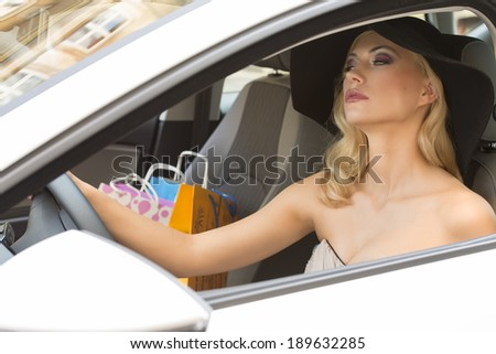 cute and sensual blond woman very elegant , driving a car with hat , she has shopping bags - stock photo