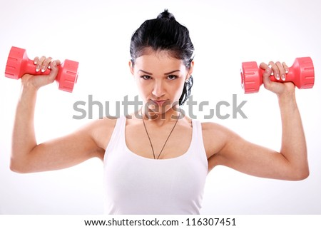 Cute and serious fitness girl lifting red dumbbells - stock photo