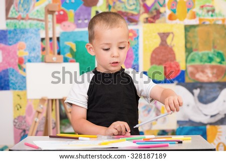 Cute and serious toddler boy is at the Art class. Looking down and painting with gray felt pen. Colorful wall and easel in background. - stock photo
