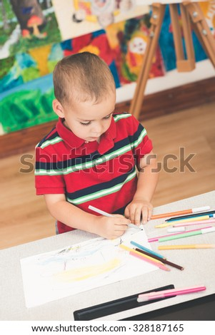 Cute and serious toddler boy is at the Art class. Looking down and painting with yellow felt pen. Colorful wall and easel in background. Photographed from above. - stock photo