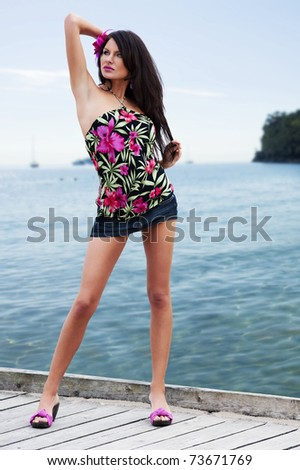 cute and sexy girl wearing mini skirt and a flower top shirt posing near the sea - stock photo