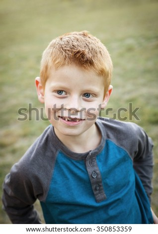 Cute and Silly Little red haired boy portrait outdoors