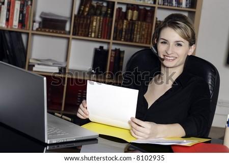 cute and smiling businesswoman at the office desk calling by phone - stock photo