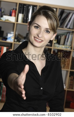 cute and smiling businesswoman at the office desk inviting you to shake her hand - stock photo