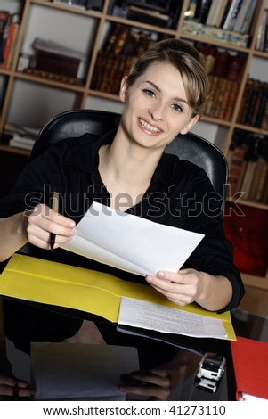 cute and smiling businesswoman at the office desk proposing you to sign a contract form - stock photo