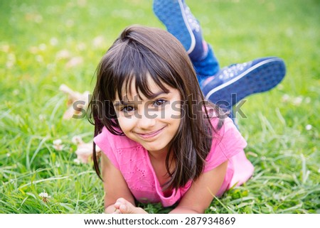 Cute and sweet girl lying in the grass smiling - stock photo