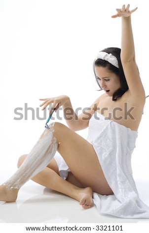 cute and young brunette dressing white towel shaving her legs with foam and making face - stock photo