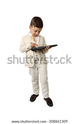 Cute Arabic looking little boy in elegant three-piece suit stands serious with tablet in hand - full height portrait isolated on white background - wealth and successful growing business concept - stock photo