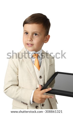 Cute Arabic looking little boy in elegant three-piece suit stands serious with tablet in hand isolated on white background - wealth and successful growing business concept - stock photo