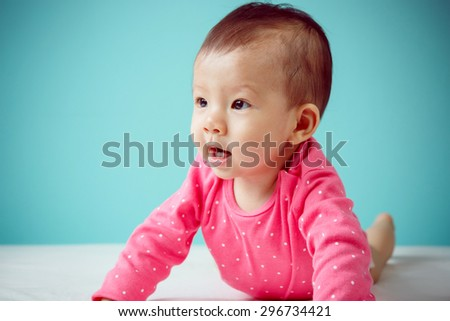 Cute Asian baby girl lying on stomach on bed, studio shot