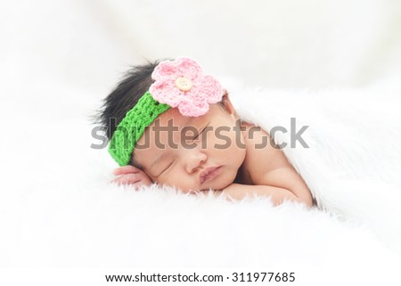 Cute asian baby girl sleeping on white cloth wearing colorful headband