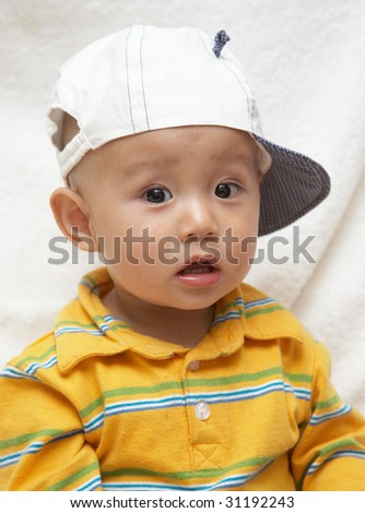 cute asian baby in a white hat - stock photo