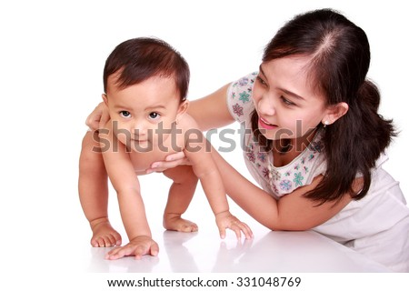 Cute Asian baby learning to walk, guided by her mother, isolated on white background - stock photo