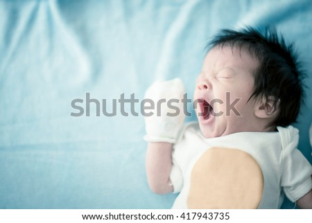 Cute asian baby newborn yawning vintage color solf blur - stock photo