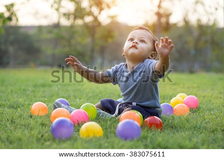 Cute asian baby playing colorful ball in green grass - Sunset filter effect - stock photo