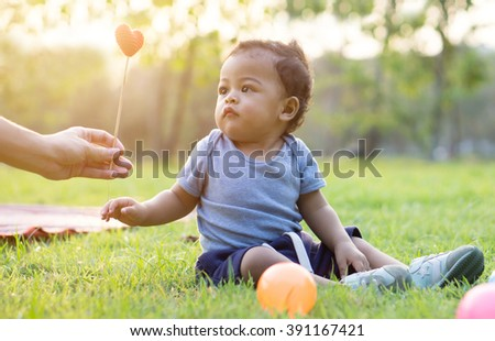 Cute asian baby Take heart from mother - Sunset filter effect - stock photo