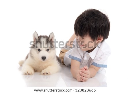 Cute asian boy and siberian husky puppy lying on white background isolated