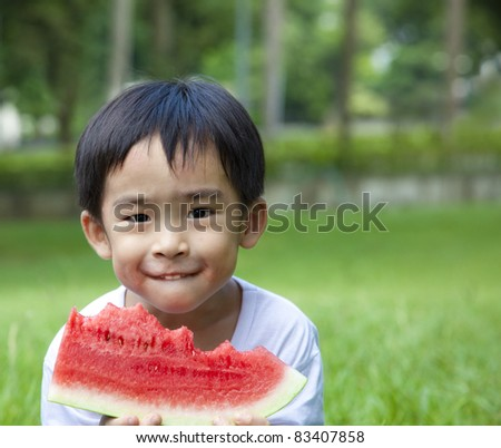 cute asian boy eating watermelon on the grass - stock photo