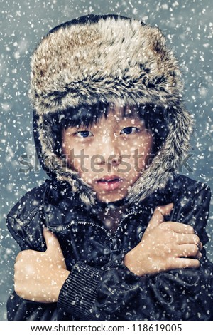 Cute Asian boy freezing in the cold during snowfall - stock photo