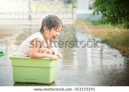 Cute asian boy has fun playing in water from a hose - stock photo