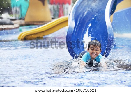 Cute asian boy having fun splashing into pool after going down water slide - stock photo