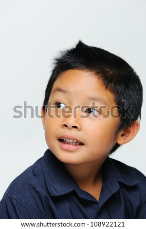 Cute asian boy looking away and smiling - stock photo