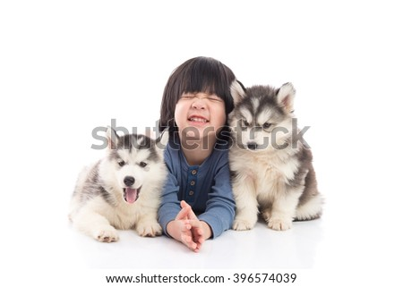 Cute asian boy lying with siberian husky puppies on white background isolated - stock photo
