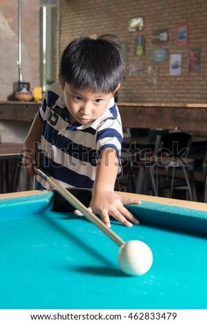 Cute asian boy playing pool in the billiard room.