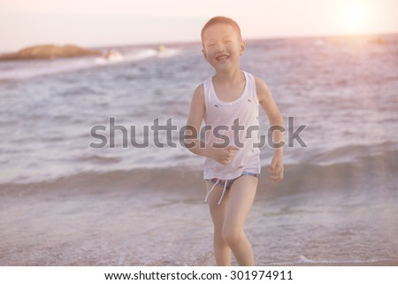 cute asian boy running on the beach in sunset,China